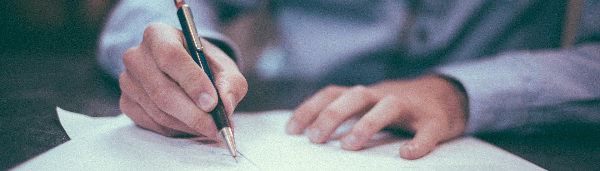 Foto: schreibende Hand mit Stift und Papier