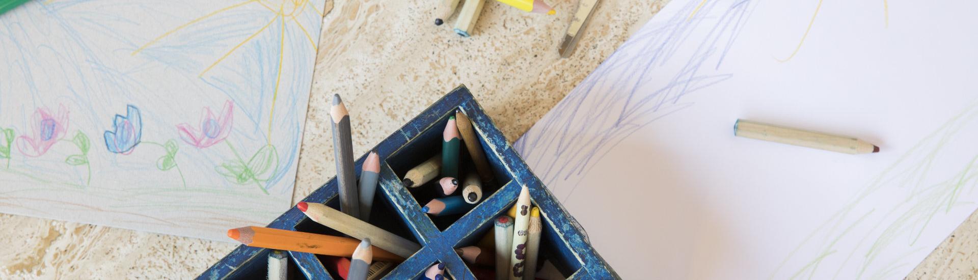 Buntstifte und Kindergemälde auf einem Tisch